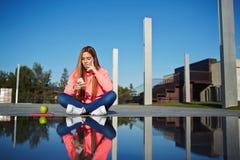Muchacha atractiva que se sienta al lado del agua con la reflexión asombrosa de su uno mismo Imagenes de archivo
