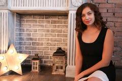 Muchacha atractiva que se sienta cerca de la chimenea Fotografía de archivo libre de regalías