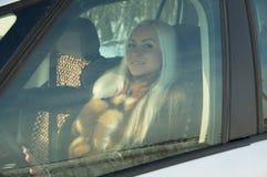 Muchacha atractiva que se sienta detrás de la rueda de un coche Imagen de archivo libre de regalías
