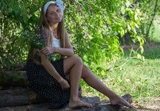 Muchacha atractiva que se sienta en la madera y que sostiene las flores Imagen de archivo libre de regalías