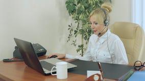 Muchacha atractiva que se sienta en oficina con los auriculares almacen de video
