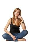 Muchacha atractiva que se sienta en piso sobre blanco Imagenes de archivo