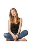 Muchacha atractiva que se sienta en piso sobre blanco Imagen de archivo libre de regalías