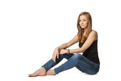 Muchacha atractiva que se sienta en piso sobre blanco Imágenes de archivo libres de regalías