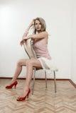 Muchacha atractiva que se sienta en silla Imagen de archivo