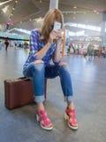 Muchacha atractiva que se sienta en una maleta en el pasillo del aeropuerto fatiga Foto de archivo libre de regalías