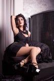 Muchacha atractiva que se sienta en una silla suave y que presenta para la cámara en un vestido oscuro con su mano para arriba Imágenes de archivo libres de regalías
