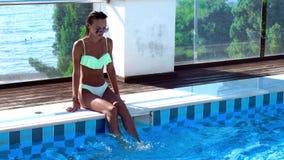 Muchacha atractiva que se sienta por la piscina almacen de video