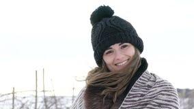 Muchacha atractiva que sonríe y que considera a la cámara el día de invierno frío ventoso almacen de video