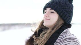 Muchacha atractiva que sonríe y que considera a la cámara el día de invierno frío ventoso almacen de metraje de vídeo