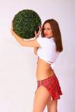 Muchacha atractiva que sostiene la bola verde Foto de archivo