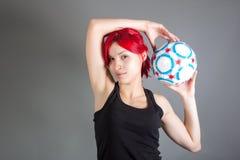 Muchacha atractiva que sostiene un balón de fútbol Fotos de archivo
