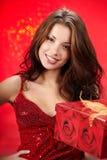 Muchacha atractiva que sostiene un regalo de la Navidad en el embalaje Fotografía de archivo