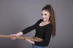 Muchacha atractiva que tira de una cuerda Imagenes de archivo