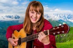 Muchacha atractiva que toca la guitarra acústica Imágenes de archivo libres de regalías