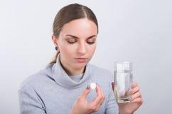 Muchacha atractiva que toma una píldora con agua en fondo ligero Fotos de archivo