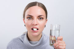 Muchacha atractiva que toma una píldora con agua en fondo ligero Imagenes de archivo