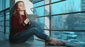 Muchacha atractiva que trabaja en el ordenador portátil que se sienta en piso por la ventana metrajes