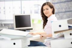 Muchacha atractiva que trabaja en la sonrisa brillante de la oficina Imágenes de archivo libres de regalías