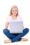 Muchacha atractiva que usa el ordenador portátil Fotografía de archivo libre de regalías