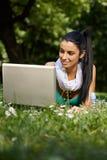 Muchacha atractiva que usa la computadora portátil en la sonrisa del parque Foto de archivo libre de regalías