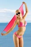 Muchacha atractiva rubia en bikiní y gafas de sol rosados Imagenes de archivo