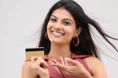 Muchacha atractiva sonriente con de la tarjeta de crédito Foto de archivo libre de regalías