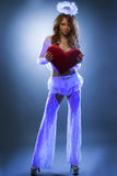 Muchacha atractiva vestida como ángel que presenta bajo luz UV Imagen de archivo libre de regalías