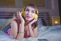 Muchacha atractiva y feliz joven en cama con los auriculares amarillos que escucha la música en Internet con el baile del teléfon Fotos de archivo libres de regalías