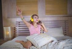 Muchacha atractiva y feliz joven en cama con los auriculares amarillos que escucha la música en Internet con el baile del teléfon Fotos de archivo