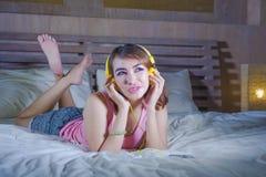 Muchacha atractiva y feliz joven en cama con los auriculares amarillos que escucha la música en Internet con el baile del teléfon Foto de archivo