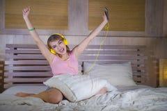 Muchacha atractiva y feliz joven en cama con los auriculares amarillos que escucha la música en Internet con el baile del teléfon Imagen de archivo