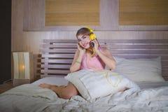 Muchacha atractiva y feliz joven en cama con los auriculares amarillos que escucha la música en Internet con el baile del teléfon Fotografía de archivo libre de regalías