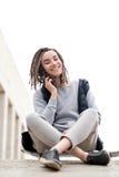 Muchacha atractiva y sonriente del adolescente que se relaja con un monopatín y que se sienta, hablando con alguien en el teléfon Fotografía de archivo