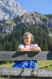 Muchacha bávara adorable en un paisaje hermoso de la montaña Imagen de archivo