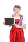 Muchacha bávara con el dirndl y tablero vacío Imagen de archivo