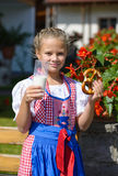 Muchacha bávara sonriente que come el pretzel y la leche de consumo en Fotos de archivo libres de regalías