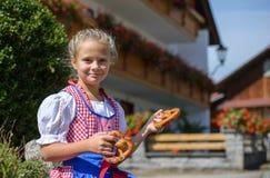 Muchacha bávara sonriente que sostiene un pretzel en manos en la granja adentro Imágenes de archivo libres de regalías