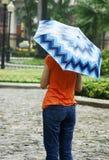 Muchacha bajo el paraguas azul en la lluvia Fotos de archivo libres de regalías