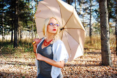 Muchacha bajo el paraguas en bosque del otoño. Foto de archivo libre de regalías