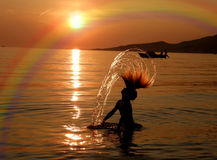 Muchacha, barco y arco iris en puesta del sol Foto de archivo
