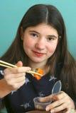 Muchacha bastante adolescente con cierre del rollo de sushi para arriba Foto de archivo