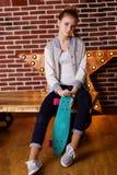 Muchacha bastante adolescente con el monopatín que se sienta en estudio Fotos de archivo