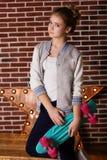 Muchacha bastante adolescente con el monopatín sobre la pared de ladrillo Imágenes de archivo libres de regalías