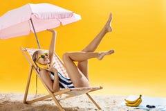 Muchacha bastante adolescente con el peinado agradable que se relaja en silla de playa Fotos de archivo