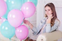 Muchacha bastante adolescente con los globos azules y rosados Imagenes de archivo