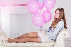 Muchacha bastante adolescente con muchos globos rosados Foto de archivo