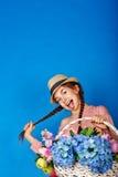 Muchacha bastante adolescente con una cesta de flores Fotografía de archivo