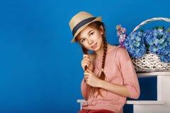 Muchacha bastante adolescente con una cesta de flores Foto de archivo libre de regalías