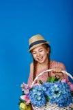 Muchacha bastante adolescente con una cesta de flores Fotos de archivo libres de regalías